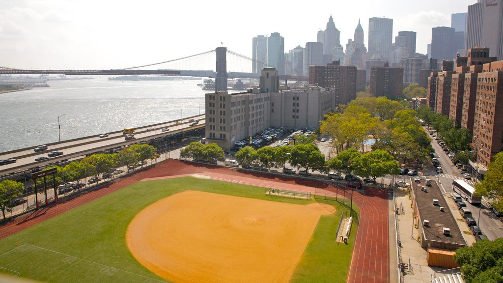 Baseball field, housing and waterside highway, East River and Brooklyn Bridge of Lower Manhattan, New York, USA