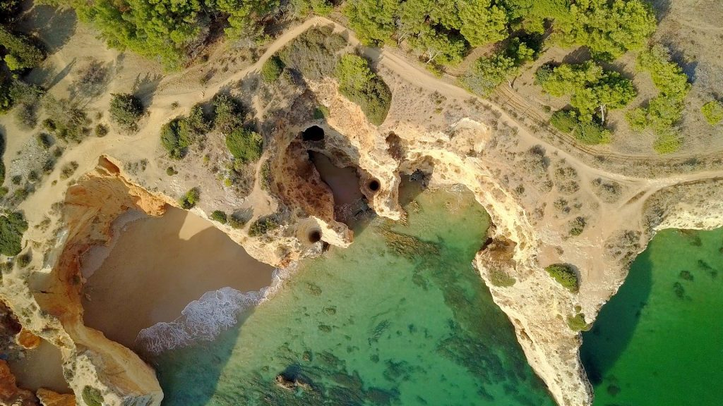 Aerial view of rough cliffs on shoreline of ocean with white sands in lagoon, Portimão, Algarve, Portugal