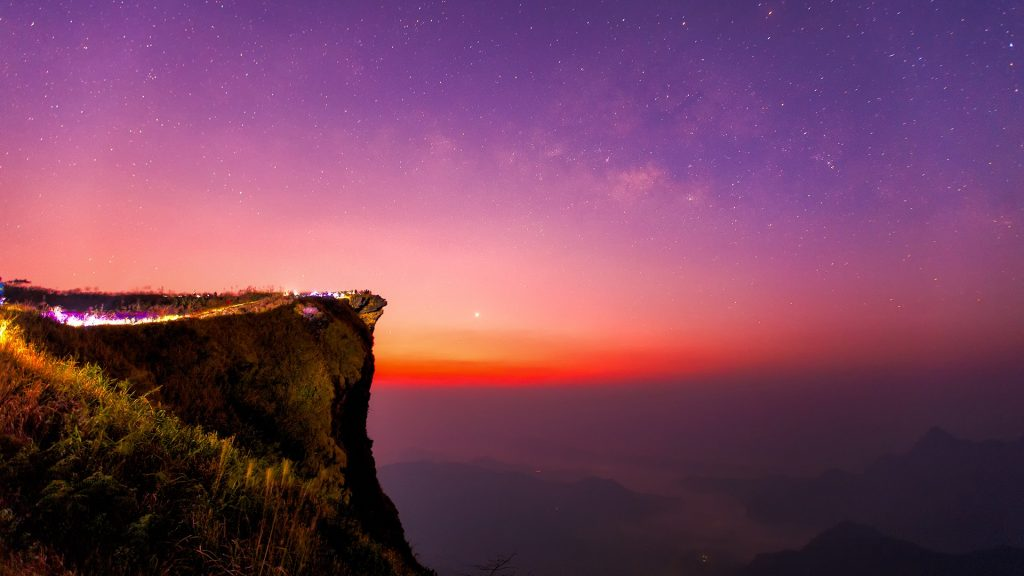Milky way and mountain range view from the peak of Phu Chi Fa hill, Chiang Rai, Thailand