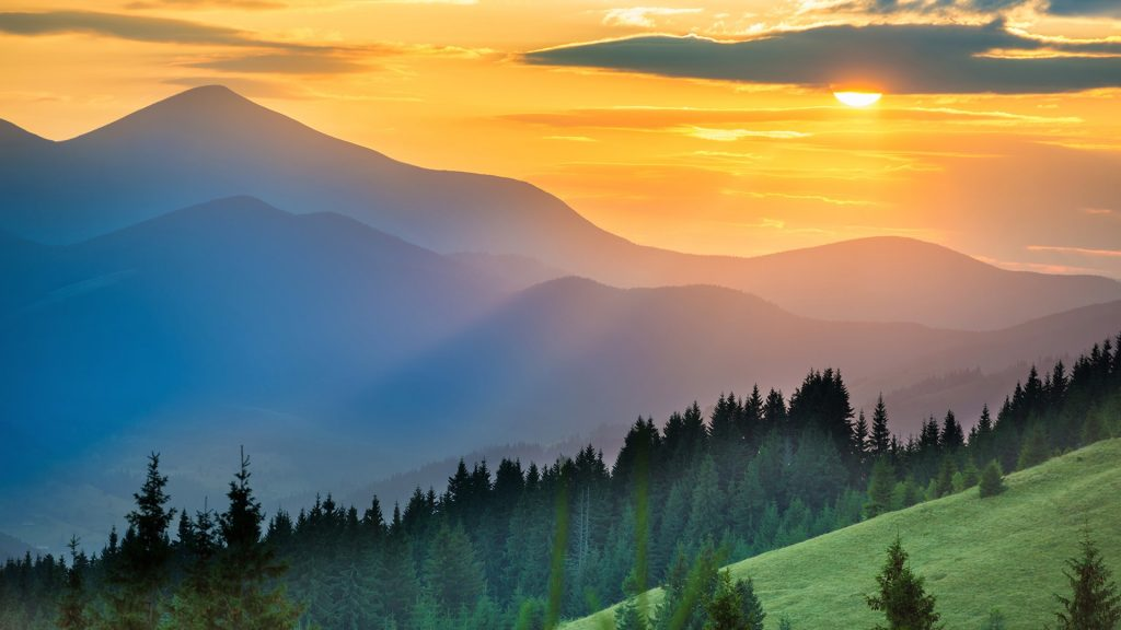 Dramatic sunset over mountains landscape with sun shining through orange clouds