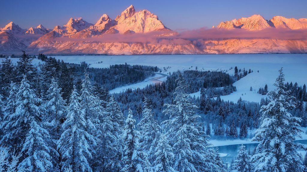 The winter sun rises over the Snake River and Teton Range, Grand Teton National Park, Wyoming, USA