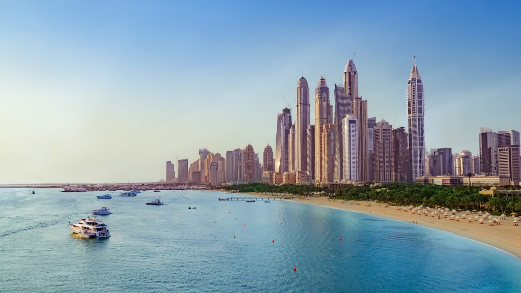 Beach with boats near Dubai Marina with view on the skyline, UAE