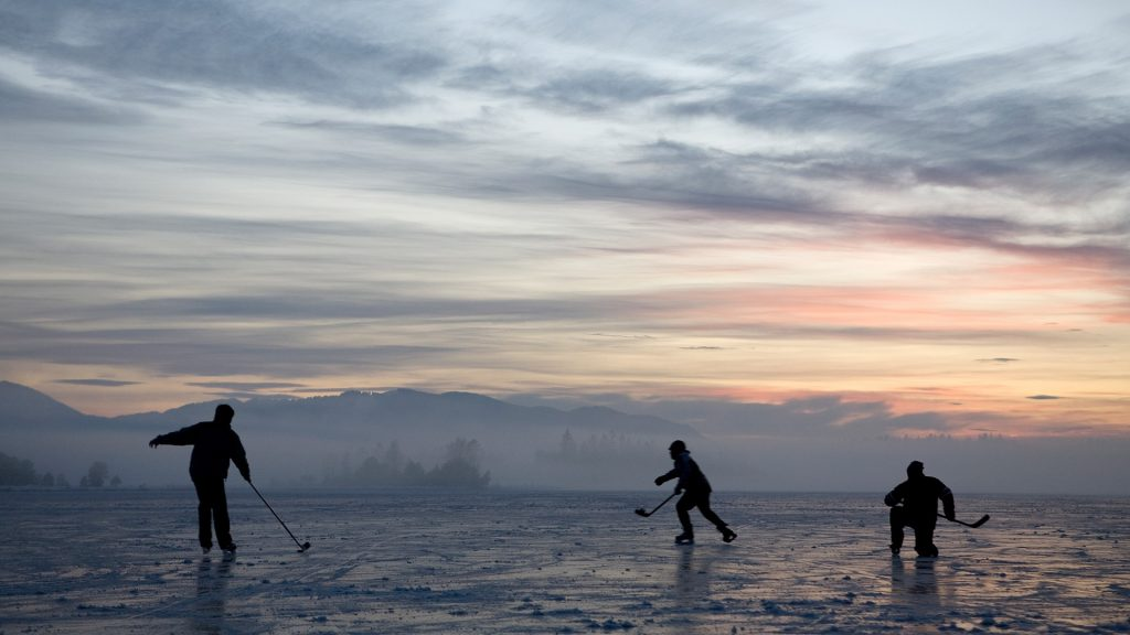 Silhouettes of kids playing hockey on frozen lake at sunset, Kirchsee, Bavaria, Germany