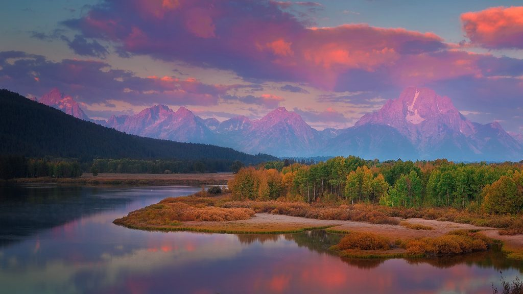 The sun rises over Oxbow Bend at the beginning of autumn, Grand Teton National Park, Wyoming, USA