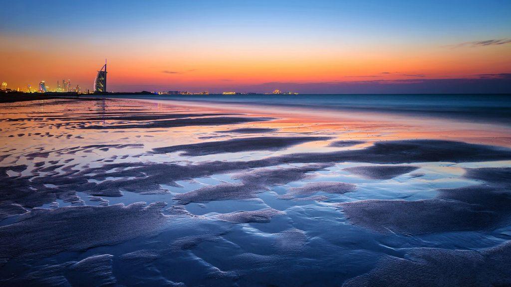 Beautiful Dubai beach in sunset light with view on a luxury modern city, UAE