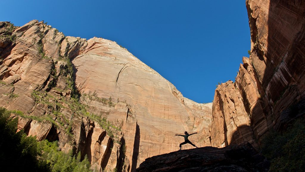 Young woman practicing yoga on a rock is silhouetted against distant cliffs, Zion, Utah, USA