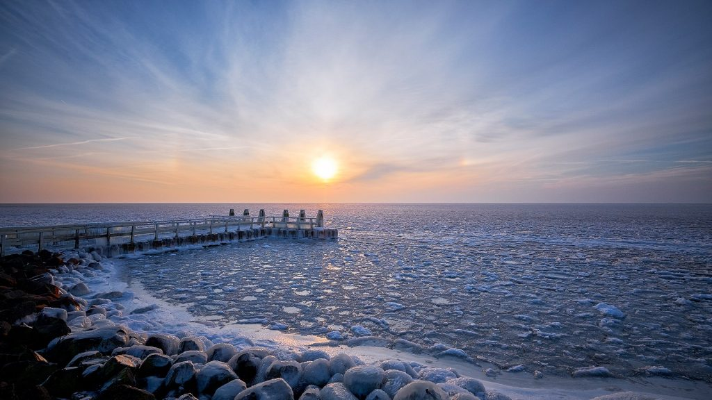 Frozen lake with an icy jetty during sunrise, north Holland, Netherlands