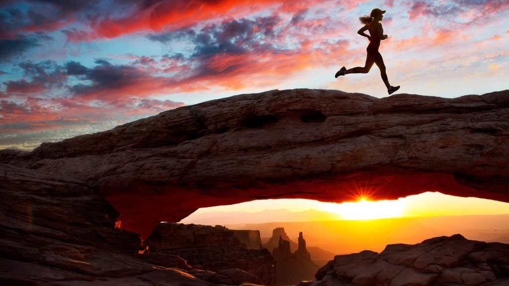 Young female runner running over Mesa Arch rock formation at sunset, Moab, Utah, USA