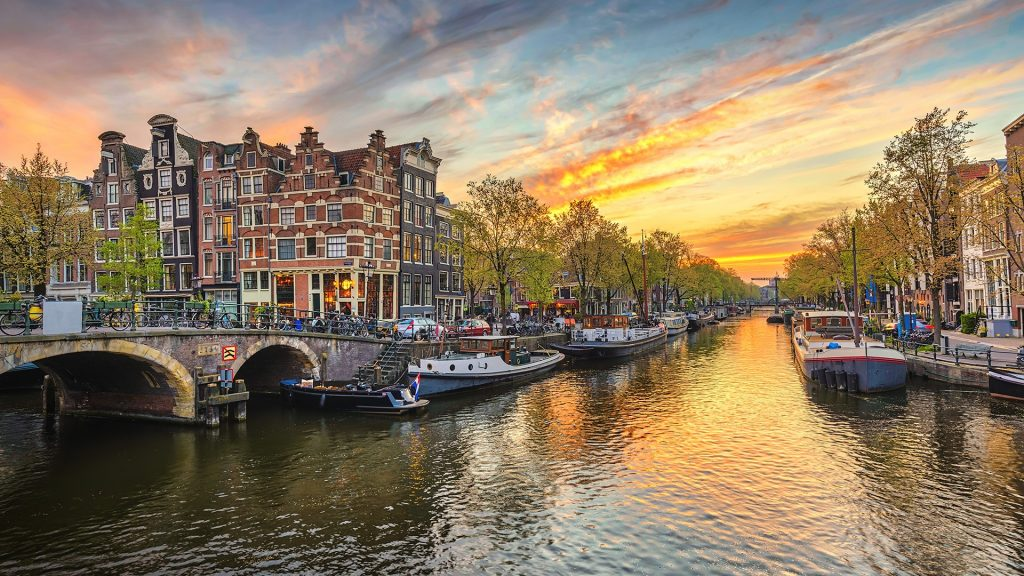 Sunset city skyline at canal waterfront, Amsterdam, Netherlands