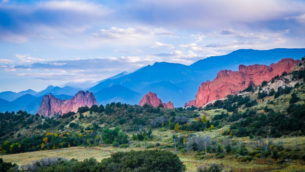 The red rock spires of the Garden of the Gods against blue mountains, Colorado Springs, USA