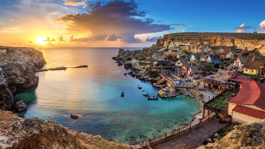 The famous Popeye Village in Anchor Bay at sunset with clouds, il-Mellieħa, Malta