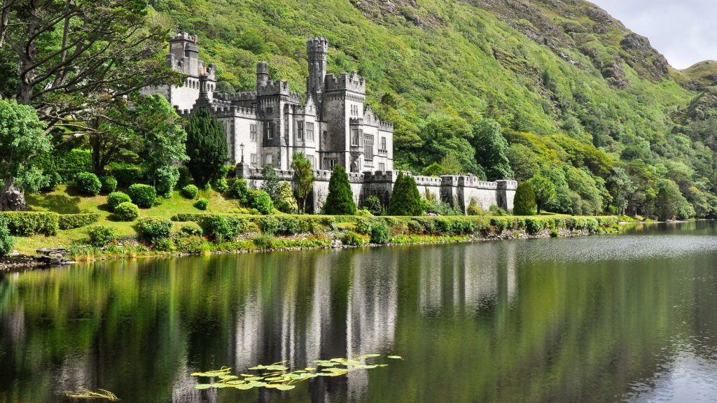 View from water at Kylemore Abbey near trees, Connemara, County Galway, Ireland
