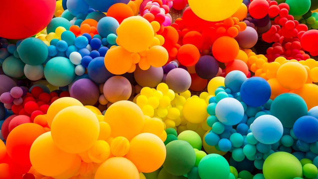 Bright abstract background of jumble of rainbow colored balloons