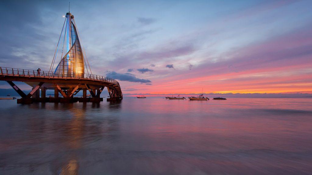 Moonrise and sunset over the pier on Los Muertos Beach, Puerto Vallarta, Mexico
