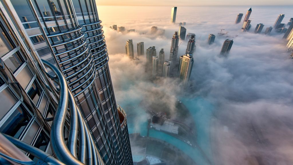 Aerial view of cityscape with skyscrapers above the clouds in Dubai, UAE