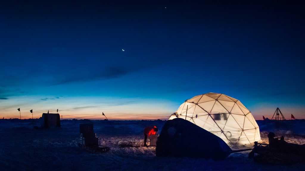 Researcher working at an ice camp under clear polar sky, Weddell Sea, Antarctica