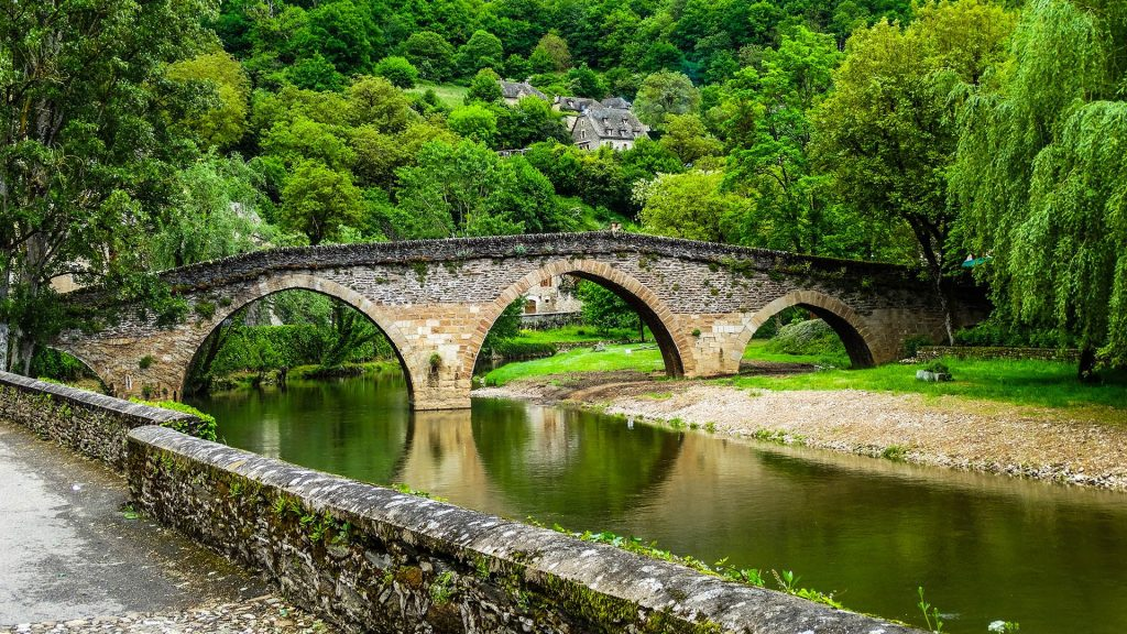 Belcastel medieval stone bridge across Aveyron river with forest, Aveyron, France