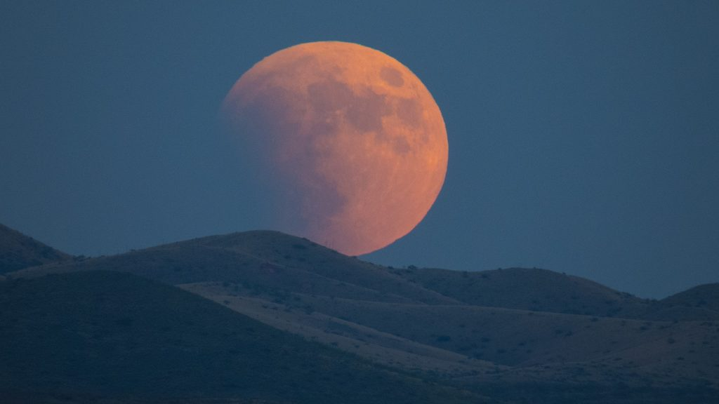 Super-blood moon rises over the Dragoon Mountains viewed from Tombstone, Arizona, USA