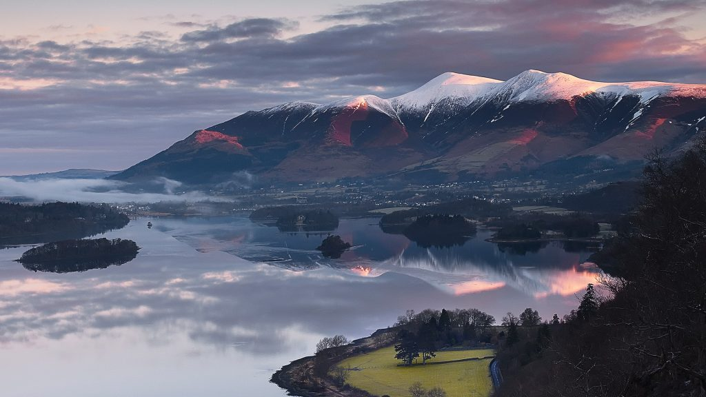 Sunrise over Skiddaw, Blencathra, Derwent Water and the town of Keswick, Cumbria, England, UK