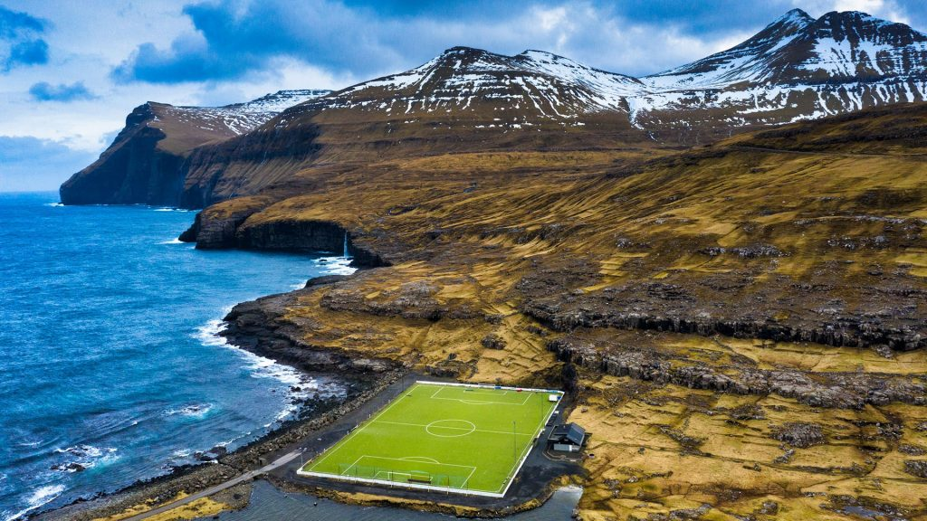Soccer field between ocean and mountains, Eidi, Eysturoy, Faroe Islands, Denmark