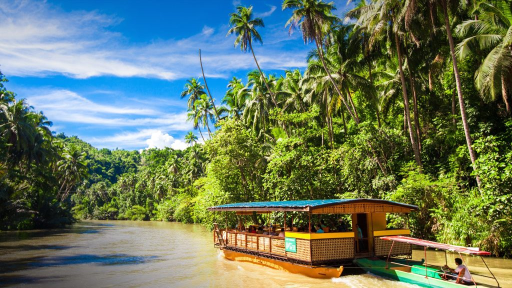 Exotic cruise boat with tourists on a jungle river Loboc, Bohol island, Philippines