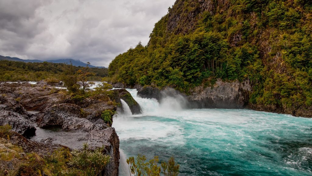 River Petrohué Waterfalls with rock formations and Osorno Volcano in background, Chile