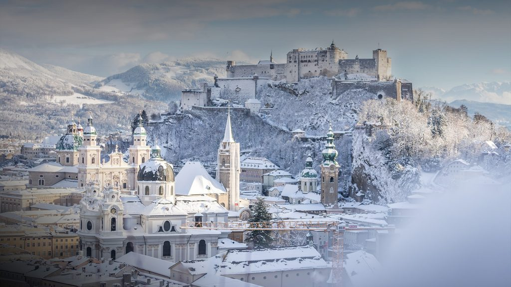 Snowy old city and fortress of Salzburg at winter sunny day, Austria