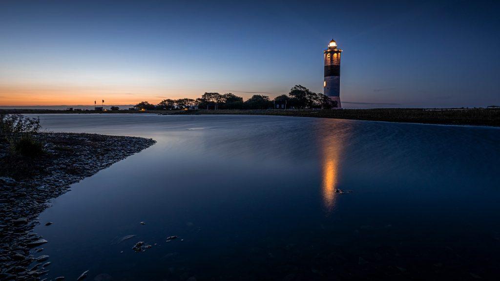 Illuminated Långe Jan lighthouse at dusk, south cape of Öland island, Sweden
