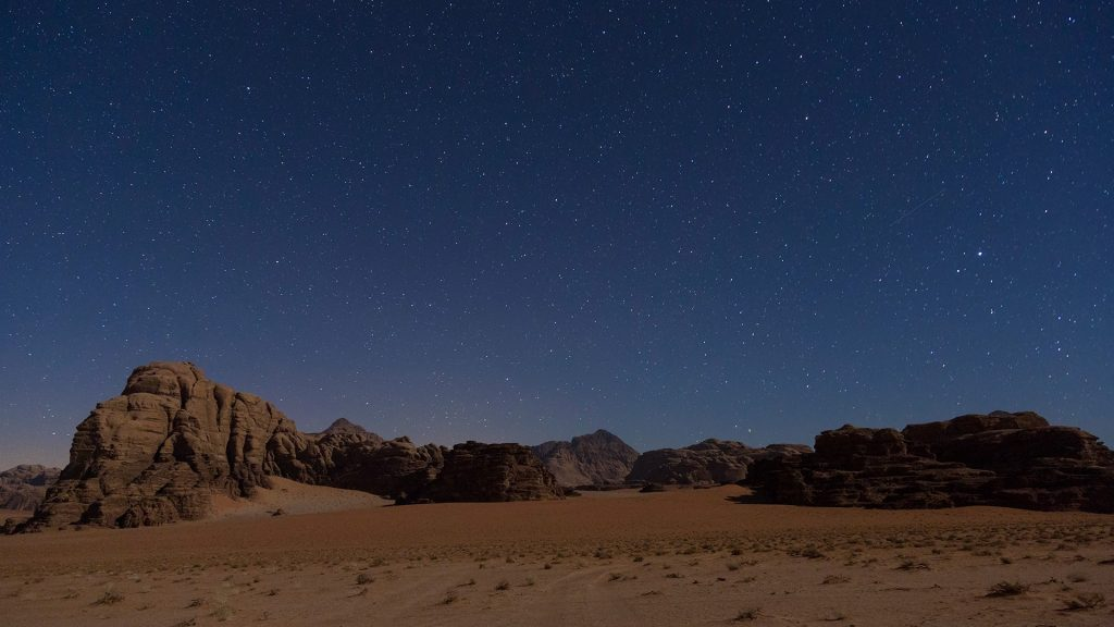 Desert landscape with rocks and mountains under a starry sky, Wadi Rum, Jordan