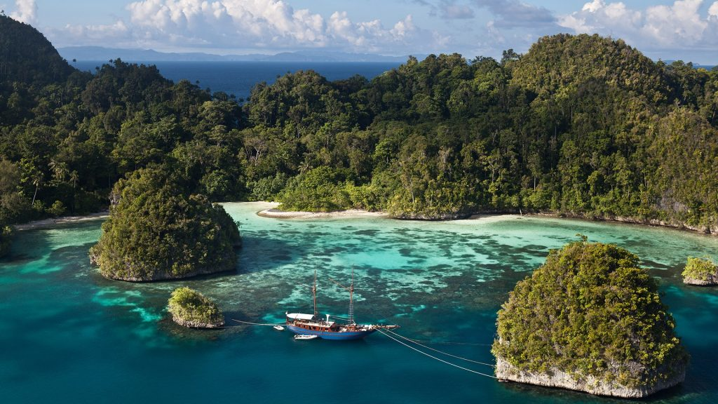 Bay with a boat between limestone islands at Raja Ampat, West Papua, Indonesia