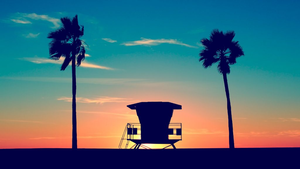 Lifeguard tower with palm trees on a beach at sunset, San Diego, California, USA