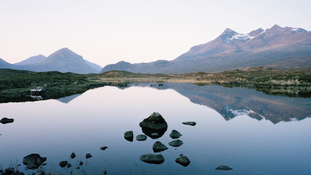 Cuillin mountain range reflected in a Loch at sunset, Isle of Skye, Highlands, Scotland, UK