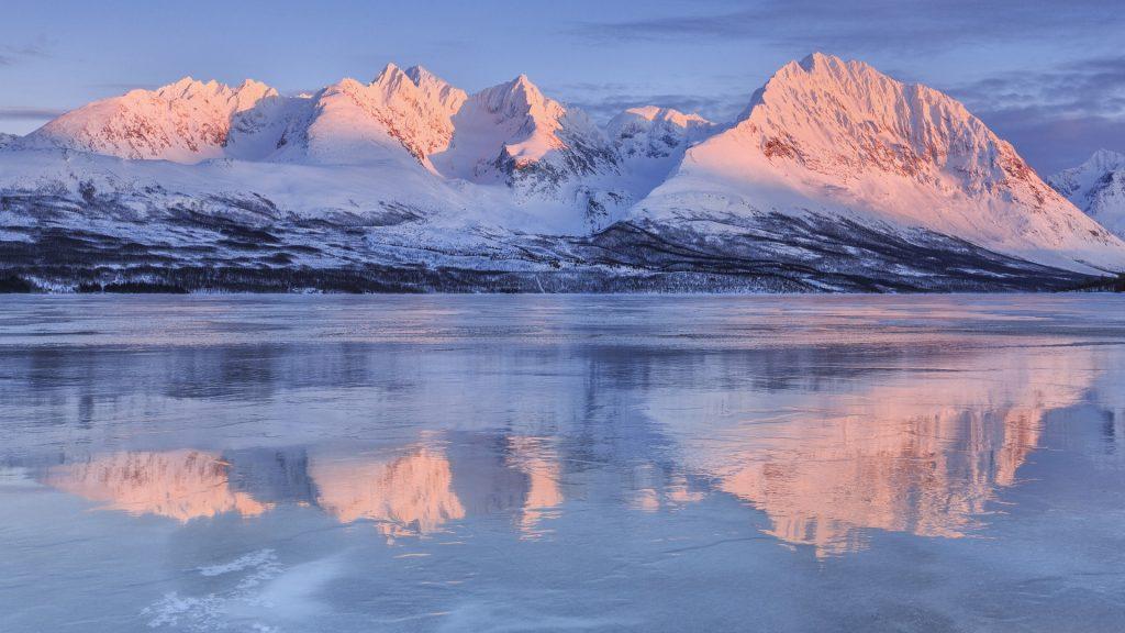 Snowy peaks at frozen Lake Jaegervatnet at sunset, Stortind, Lyngen Alps, Troms, Lapland, Norway