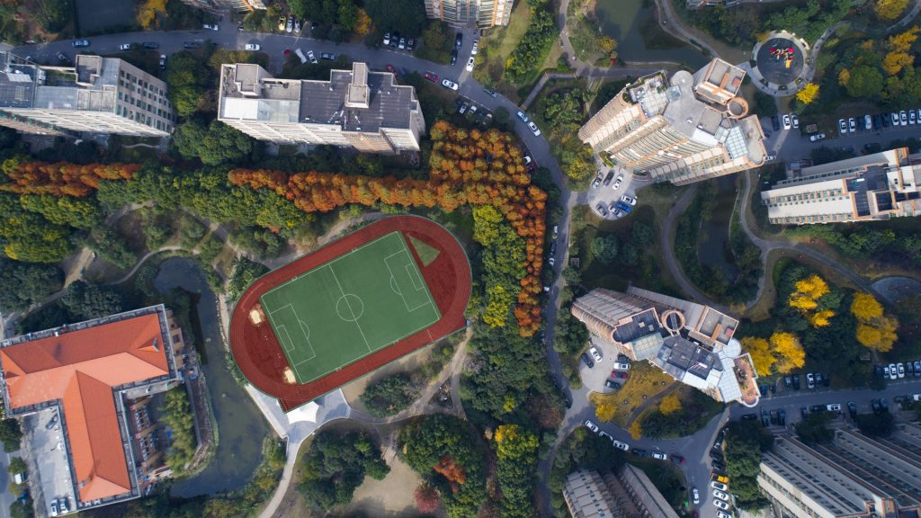 Aerial view of football field between residential buildings, Shanghai Pudong district, China