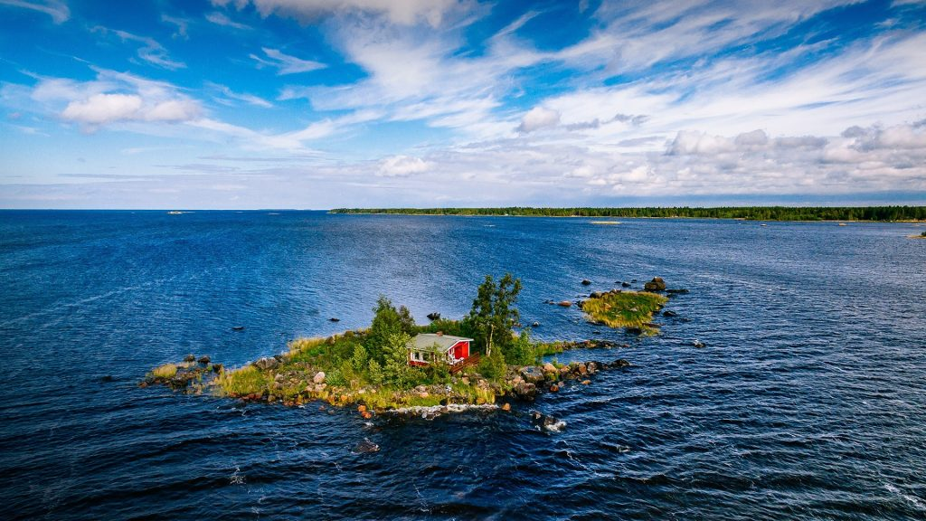 A small red cottage on an island in the blue sea on a summer day, Finland