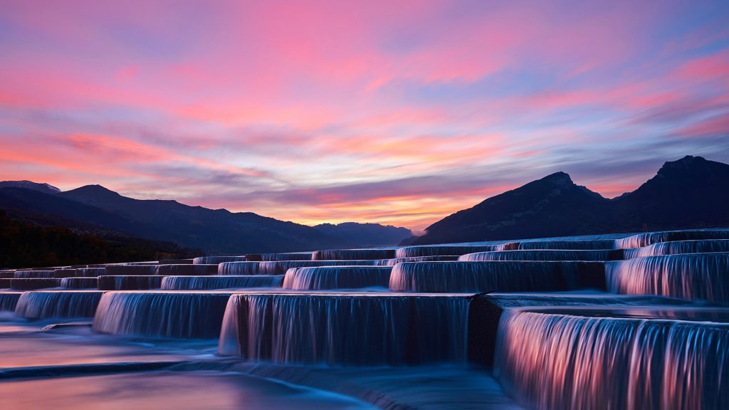 View of stepped waterfall group at sunrise in pink sky, China